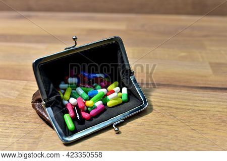 Pills In Wallet On Wooden Background. Multicolored Pharmaceutical Pills, Medical Tablets And Capsule