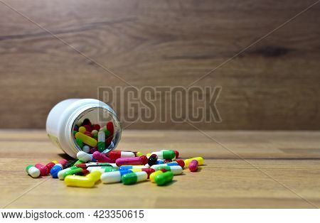 Pills From A Plastic Bottle On Wooden Background. Multicolored Pharmaceutical Pills, Medical Tablets