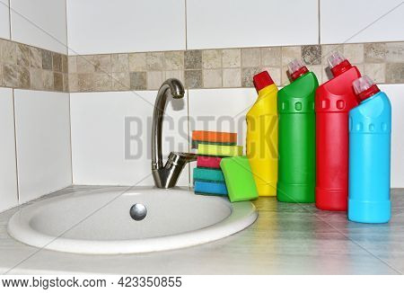 Detergent Bottles And Sponge Near The Kitchen Sink At Home. Detergents And Laundry Concept.