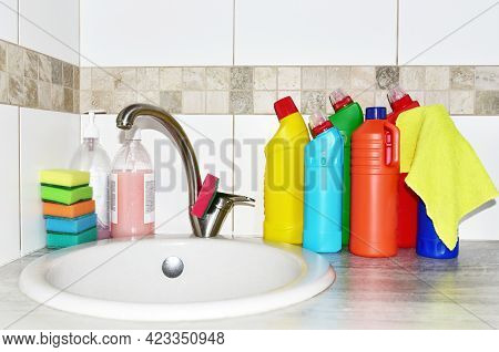 Detergent Bottles And Sponge Near The Kitchen Sink At Home. Detergents And Laundry Concept. Kitchen