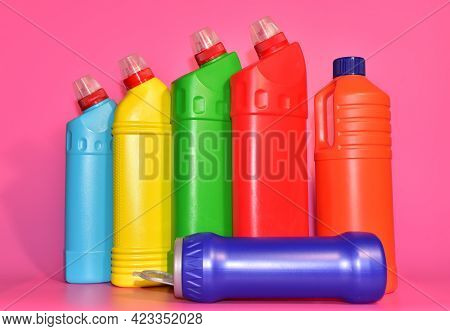 Detergent Bottles On Pink Background. Detergents And Laundry For Cleaning. Household Chemicals Conce