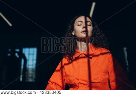 Young Woman In Orange Suit. Female In Orange Color Overalls At Jail