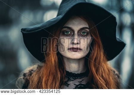 Halloween. A portrait of an angry witch near the forest. Magic, dark force, spell.