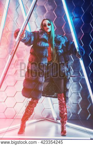 Modern fur coat fashion. Full length portrait of a stunning fashion model girl in expensive silver fox fur coat posing among the neon lamps. Futurism, techno style.