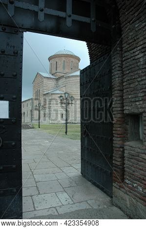 The Open Steel Door Of The Gate Leading To The Ancient Medieval Temple. A Brick Wall Enclosing A Med