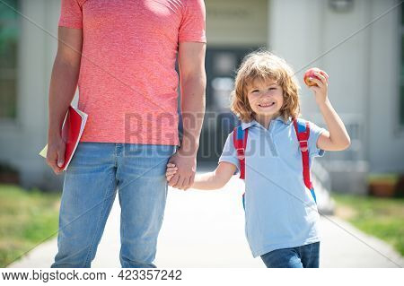 Father Walking Son To School. Parent And Pupil Of Primary School Schoolboy Holding Hand Walking Up E