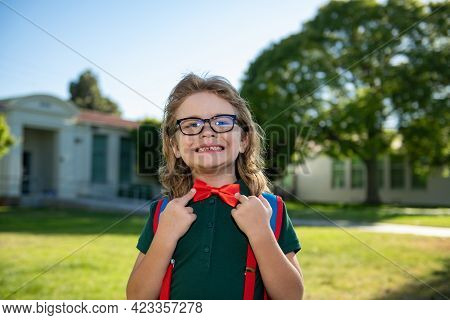 Portrait Of Schoolboy With Backpack Near School Outdoors. Nerd Pupil Ties A Bowtie, Correcting Red B
