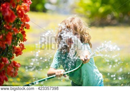 Kids Play With Water Garden Hose In Yard. Outdoor Children Summer Fun. Little Boy Playing With Water