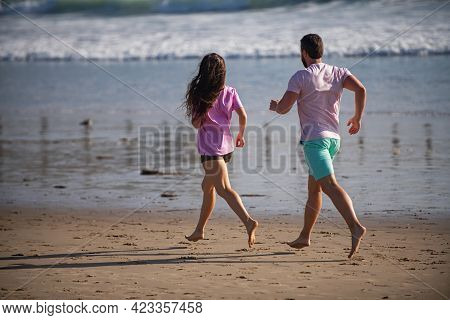 Couple Running On Beach. Running People Jogging On Beach Exercising And Jogging Training. Sport Runn