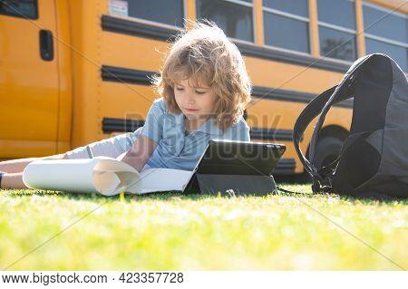Cute Schoolboy Laying On Grass In The Park Near School Bus. School Kid Outdoor.