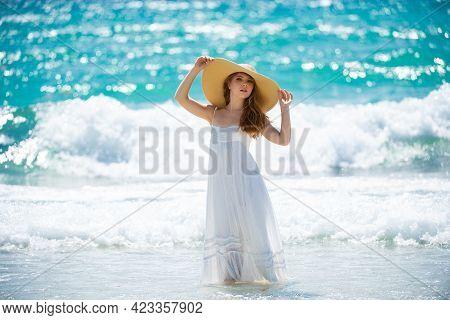 Sensual Girl With Straw Hat Enjoying Sunbath At Beach. Sexy Tanned Woman Enjoying Breeze At Seaside.