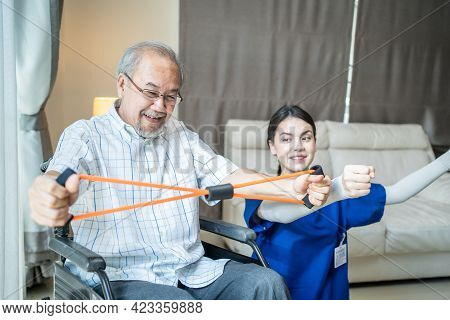 Asian Disabled Senior Elderly Man On Wheelchair Doing Physiotherapist With Support From Therapist Nu