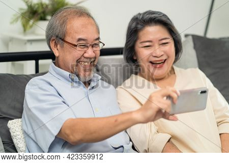 Asian Beautiful Old Woman And Senior Man Couple In Love Using Mobile Phone For Video Call With Son,