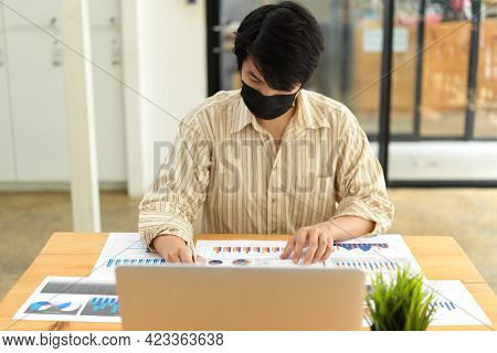 Portrait Of Businessman With Face Mask Working With Paperwork And Laptop In Office Room