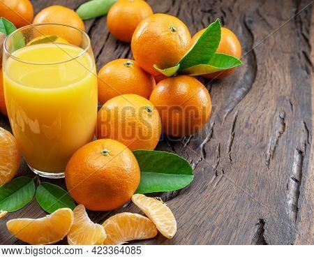 Orange tangerine fruits and glass of fresh tangerine juice on dark wooden background.