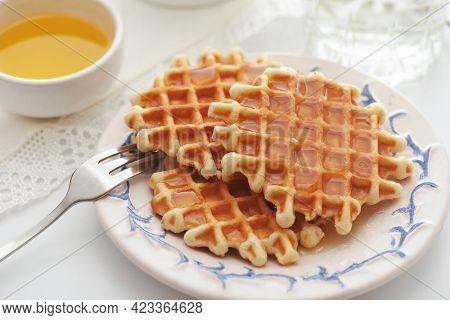 Freshly baked homemade belgian waffles with honey on white table