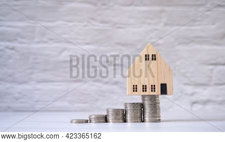 House And Coin Placed On The Table As A Ladder Represent Interest Rates. Concept Of Investment Real