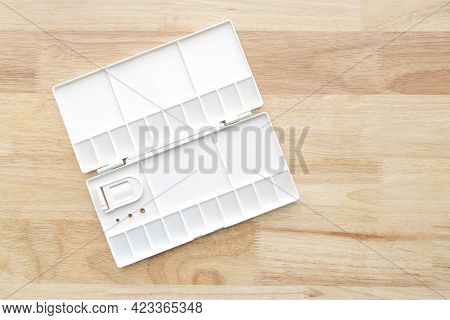 White Watercolour Palette. Empty Watercolor Tray Isolated On Wood Background. White Plastic Paint Pa
