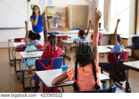 Rear view of students raising their hands while sitting on their desk in the class at school. school and education concept