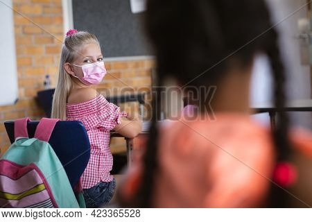 Caucasian girl wearing face mask sitting on her desk in the class at school. education back to school health safety during covid19 coronavirus pandemic