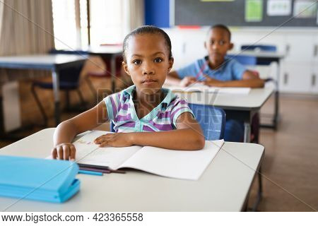 Portrait of african american girl sitting on her desk in the class at school. school and education concept