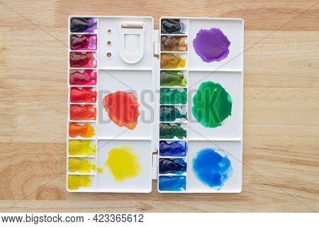 Colorful Watercolor Paints Set In Watercolour Palette On Wood. Bright Multicolored Aquarelle Paints