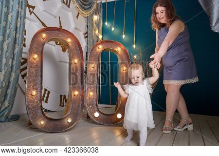 Portrait Of A Little Blonde Girl And Plumb Chubby Mother In Beautiful Dress. Family In Studio During