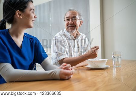 Asian Young Woman Nurse Taking Care Of Disabled Handicapped Senior Elderly Man At Nursing Home. Care