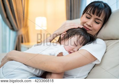 Asian Beautiful Loving Mother Hugging Sleeping Baby Girl In Her Arms With Gently. Parent Holding Sma