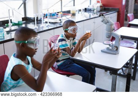 Two african american boys wearing protective glasses holding a beaker in science class at laboratory. school and education concept