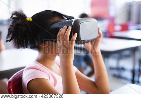 African american girl wearing vr headset while sitting on her desk in the class at school. school and education concept