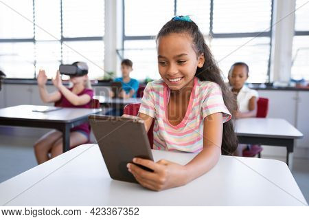 Smiling african american girl using digital tablet while sitting on her desk in class at school. school and education concept