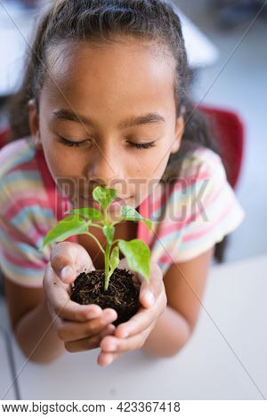 Close up of african american girl with eyes closed holding a plant seedling in the class at school. school and education concept