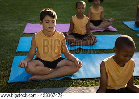Caucasian boy practicing yoga and meditating sitting on yoga mat in garden at school. school and education concept