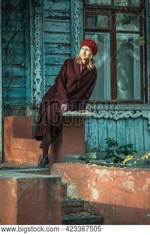 A woman in a burgundy coat and beret sitting on porch of old wooden house.