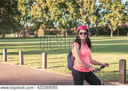 Portrait Of A Young Woman Wearing Sunglasses With Pink Top And Bike Helmet During Her Scooter Ride T