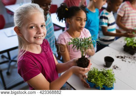 Portrait of caucasian girl smiling while holding a plant seedling in the class at school. school and education concept