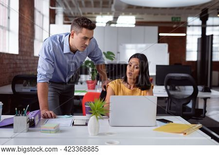 Caucasian male and female business colleague in discussion at desk in office, looking at laptop. working in business at a modern office.