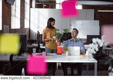 Happy caucasian male and female colleague talking in office, laughing and drinking coffee. working in business at a modern office.