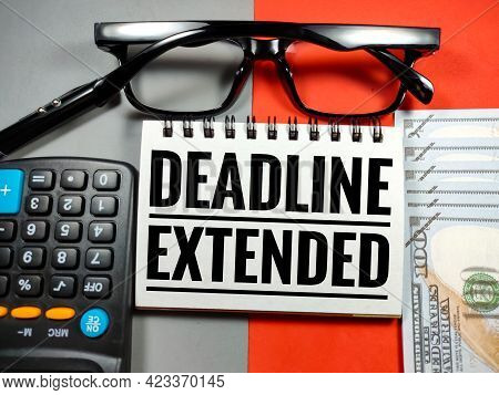 Business Concept.text Deadline Extended With Glasses,calculator,pen And Banknote On Gray And Red Bac