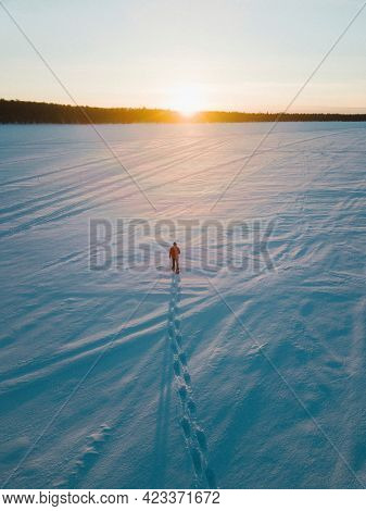 Man walking on the snow while admiring the sunset