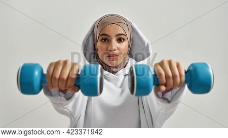 Young Arabic Woman In Hijab And Hoodie Holding Dumbbells In Front Of Her While Posing On Light Backg
