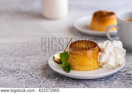 Creme Caramel Dessert Or Flan  Decorated  With Whipped Cream And Mint  And Served With Cup Of Coffee