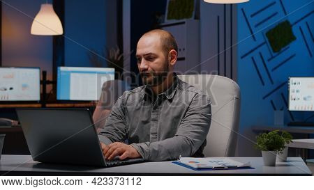 Overworked Businessman Typing Financial Statistics On Laptop Sitting At Desk Table In Startup Compan