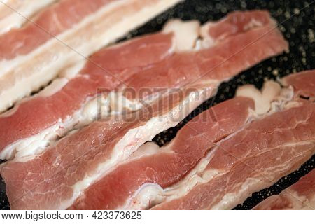 Close-up View Of Bacon Slices In Frying Pan.