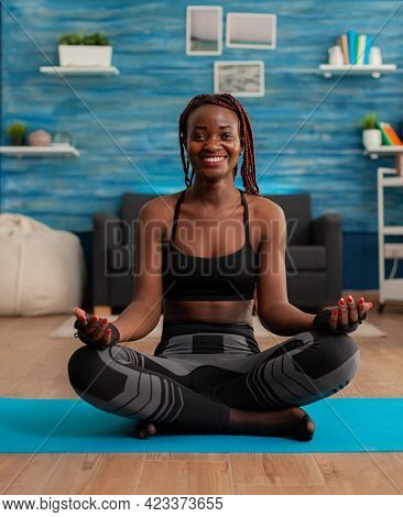 Portrait Of Black Woman Smiling Practicing Yoga At Home Sitting In Lotus Pose On Mat Mediting, Pract