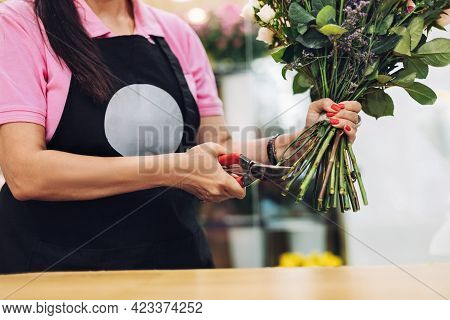 A Professional Female Florist In An Apron Cuts The Stem Of Flowers With Scissors At The Table. The C