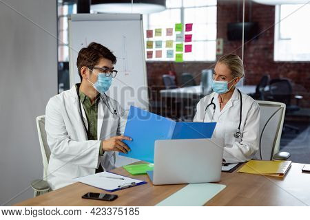 Diverse male and female doctor wearing face masks sitting in hospital office discussing paperwork. medical and healthcare services during coronavirus covid 19 pandemic.
