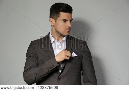 Man Fixing Handkerchief In Breast Pocket Of His Suit On Light Grey Background