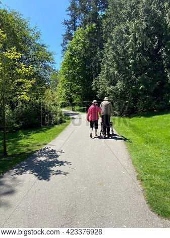 Senior couple walking through a quiet summer park. Retired man and women taking a stroll with a walker outside.